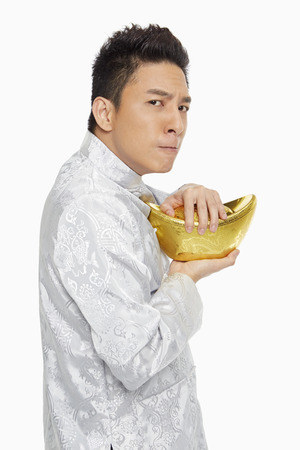 Man in traditional clothing holding on tightly to a gold ingot photo