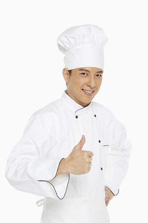 only mid adult men: Cheerful chef showing hand gesture