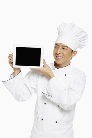 Chef holding up a digital tablet photo
