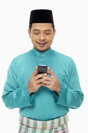 Man in traditional clothing sending a text message