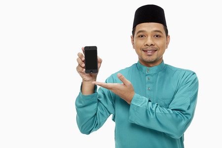 Man in traditional clothing holding up a mobile phone