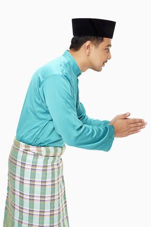 伝統的な服の表示手ジェスチャーを挨拶の男