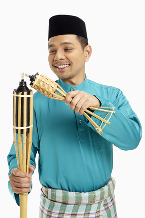 malaysia culture: Man in traditional clothing lighting up the bamboo torches