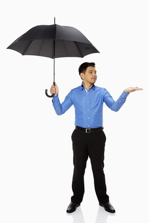 Businessman holding out his hand while carrying an umbrella photo