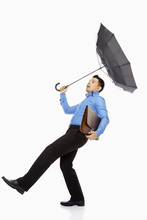 Businessman with umbrella and briefcase being blown away photo