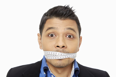 Businessman with a measuring tape wrapped around his mouth photo