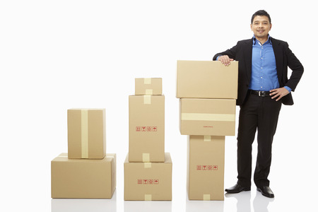 out of order: Businessman standing beside a stack of cardboard boxes