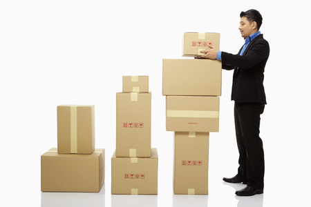 Businessman placing a box on top of a stack of boxes