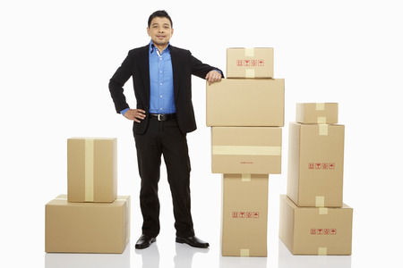 relocate: Businessman standing beside a stack of cardboard boxes