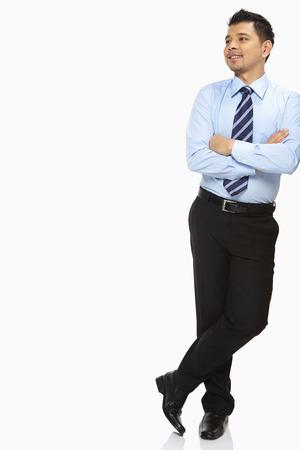 business smile: Hombre de negocios apoyado contra una pared