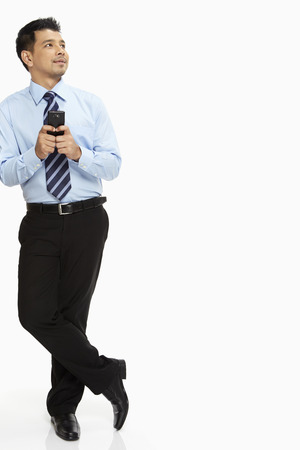 Businessman leaning against a wall, text messaging photo