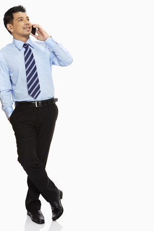 well dressed  holding: Businessman leaning against a wall, talking on mobile phone Stock Photo