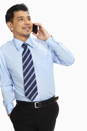 Businessman leaning against a wall, talking on mobile phone photo