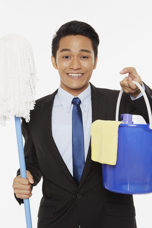 cleaning supplies: Businessman holding up a mop and other cleaning supplies