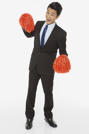 Businessman holding up red pom poms photo