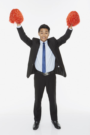 Businessman holding up red pom poms Stock Photo