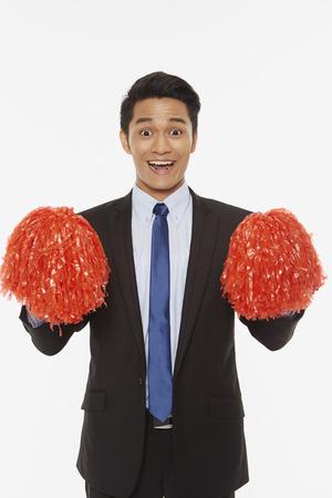 pom poms: Businessman holding up red pom poms Stock Photo