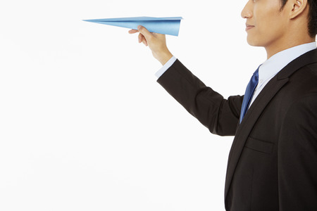 Businessman holding a paper airplane photo