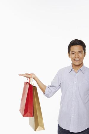 Mens met het winkelen zakken die handgebaar tonen