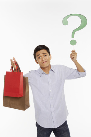 Man with shopping bags holding up a question mark photo