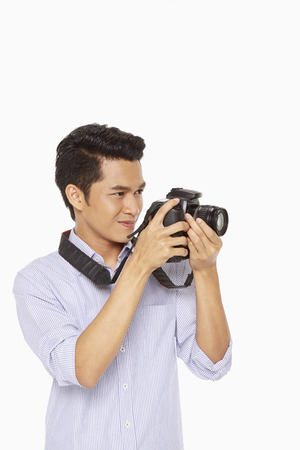 Man taking pictures with a digital camera photo