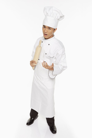 Male chef singing into a rolling pin photo