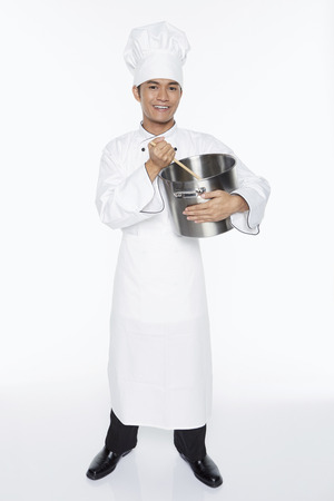 stirring: Cheerful male chef stirring