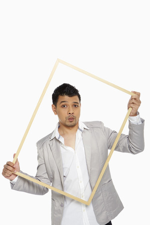 puckering lips: Man holding up a wooden picture frame, making a face Stock Photo