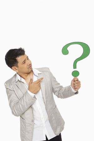 Man holding up a question mark symbol photo