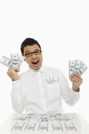 Man holding piles of cash photo