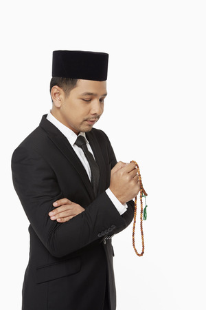 Businessman praying with prayer beads photo