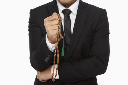 Businessman praying with prayer beads