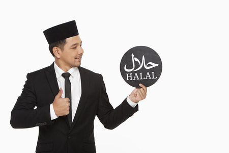 Businessman holding up a Halal sign photo