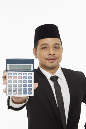 Businessman holding up a calculator photo