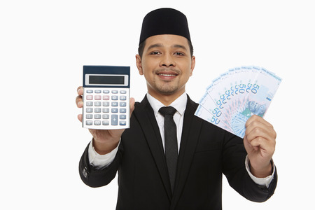 Businessman holding up a calculator along with a pile of cash photo