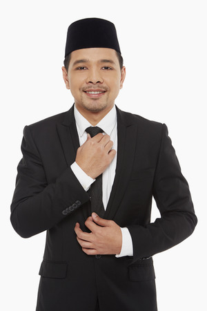 Businessman adjusting his neck tie photo