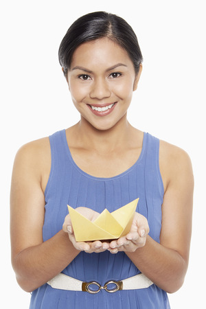Cheerful woman holding a paper boat photo