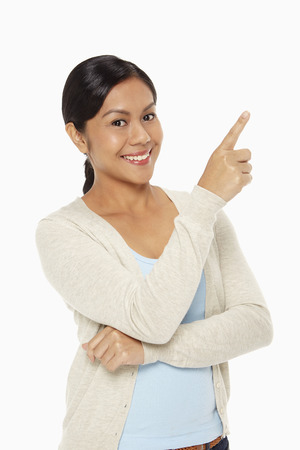 Woman smiling and pointing above photo