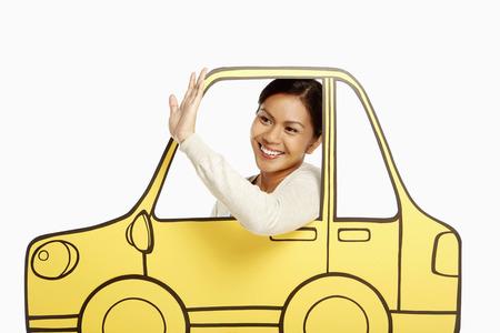 Friendly woman waving from inside a cardboard car photo