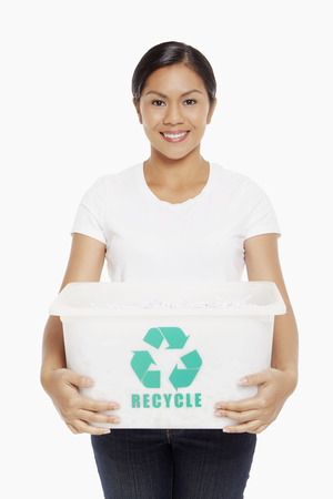 Woman carrying a plastic box with a Recycle logo on it photo