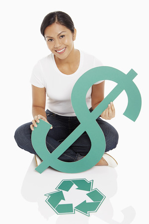 recycle logo: Cheerful woman holding up a dollar sign, with Recycle logo placed on floor Stock Photo