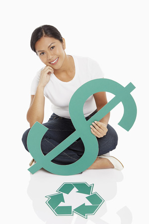 Cheerful woman holding up a dollar sign, with Recycle logo placed on floor photo