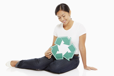 Woman holding up a Recycle logo photo