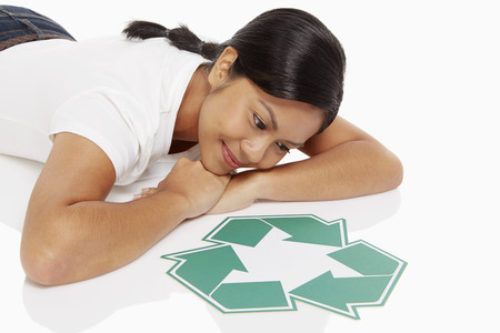 recycle logo: Woman lying on front, looking at a Recycle logo