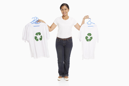 recycle logo: Woman holding up t-shirts with a Recycle logo on it
