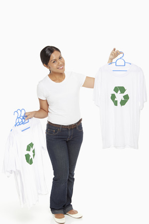 Woman holding up t-shirts with a Recycle logo on it photo