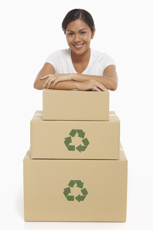 Cheerful woman resting her arms on a stack of cardboard boxes photo