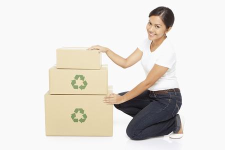 woman kneeling: Woman kneeling beside a stack of cardboard boxes