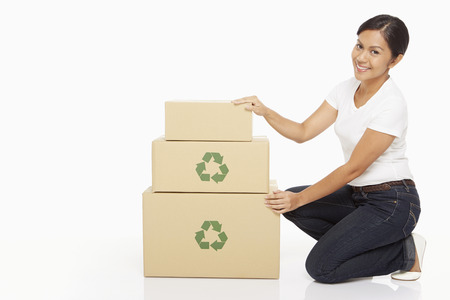 Woman kneeling beside a stack of cardboard boxes photo