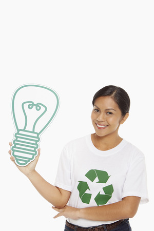Happy woman holding up a cardboard light bulb photo